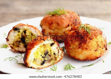 Fried meat balls stuffed with grated cheese and fried mushrooms. Stuffed meat patties on a plate and on wooden background. Home cuisine recipe. Closeup