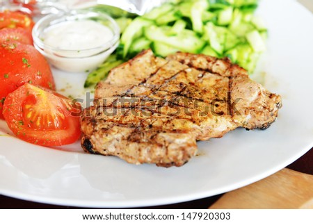fried meat, sauce and slices of tomato