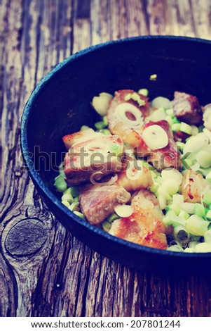 Fried meat with onion in a frying pan - stock photo