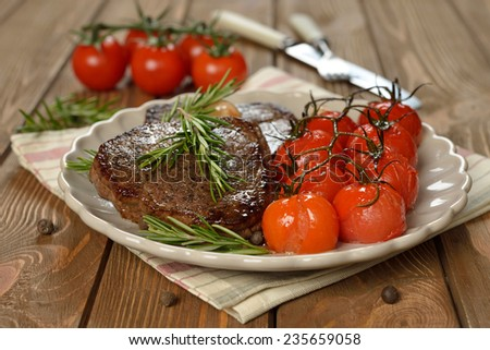 Fried meat with rosemary and cherry tomatoes - stock photo