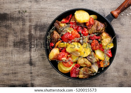 Fried meat with vegetables in a cast iron pan on a wooden table, top view with copy space