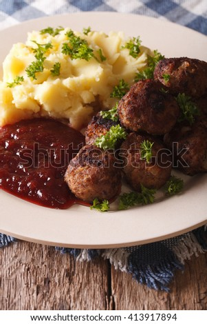 fried meatballs, lingonberry sauce with potato garnish on a plate close-up. Vertical - stock photo