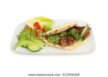 Fried minute steak in a flatbread kebab style with salad on a plate isolated against white - stock photo