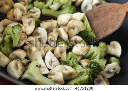 Fried mushrooms and broccoli in a wok