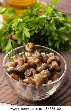 Fried mushrooms in  bowl on wooden table. Selective focus. - stock photo