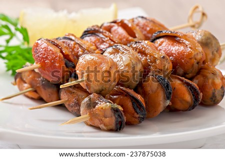 Fried mussels with onions on skewers with lemon and parsley - stock photo
