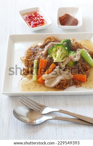 Fried noodle in gravy with pork and broccoli , carrot vegetable