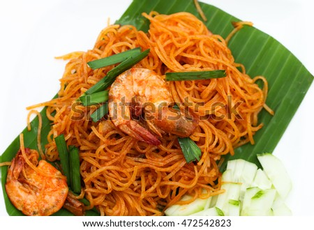 Fried noodle Thai style with prawns, Stir fry noodles with shrimp in Pad Thai style serve on banana leaf. Top view isolate white plate background.