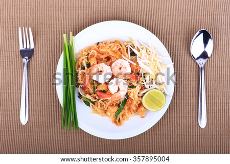 Fried noodle Thai style with prawns, Stir fry noodles with shrimp in padthai style on table. Top view isolate white - stock photo