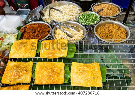 Fried noodle wrapped with eggs, Thai style food , Pad thai - stock photo