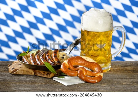 Fried Nuremberg sausages on sauerkraut with a mug of Bavarian beer and a pretzel - stock photo