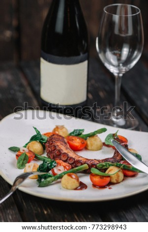Fried octopus tentacles with wineglass and bottle of wine on white plate on dark wood background