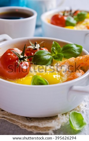 Fried of quail eggs with tomatoes, shrimp and cheese in a batch manner. Selektivgy focus. - stock photo