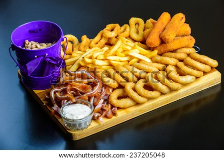 fried onion rings, Colmar, cheese, french fries, peanuts, pork ears on a wooden board - stock photo