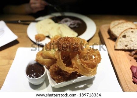 Fried onion rings in crispy dough with homemade plum sauce in a czech pub