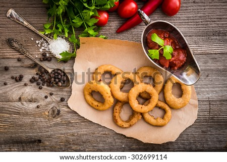 fried onion rings on parchment with sauce and vegetables on a wooden background - stock photo