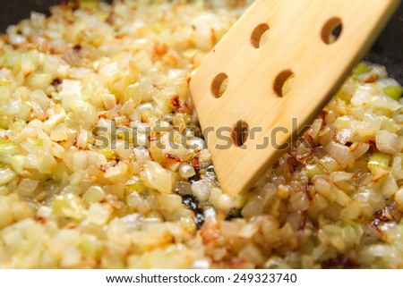 Fried onions and a wooden paddle - stock photo