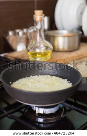 Fried onions in a frying pan, which stands on a gas stove