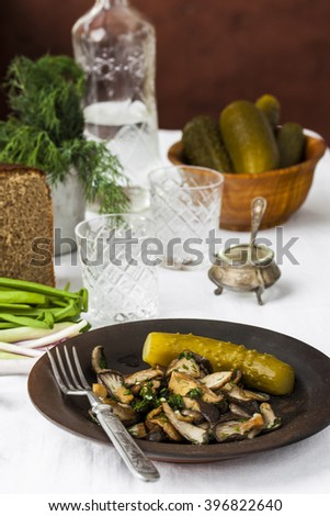 fried oyster mushrooms with garlic and pickled cucumber on the table - stock photo