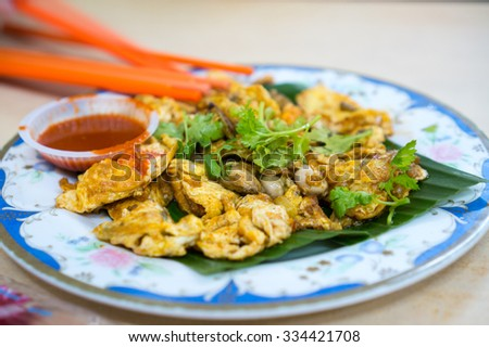 Fried oysters with egg garnished with celery