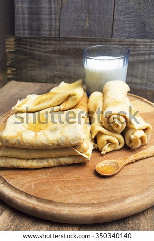 Fried pancakes on old wooden table. glass of milk