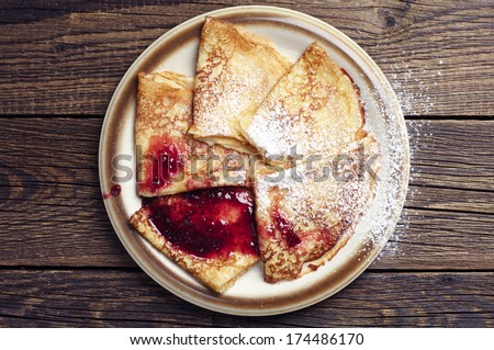 Fried pancakes with jam on vintage wooden background. Top view  - stock photo