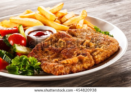 Fried pork chop, French fries and vegetable salad  - stock photo
