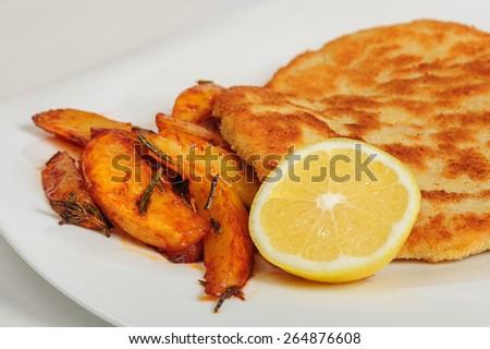 Fried pork chop schitzel with sliced potato - stock photo
