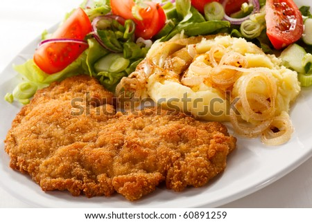 Fried pork chop with potatoes and vegetable salad