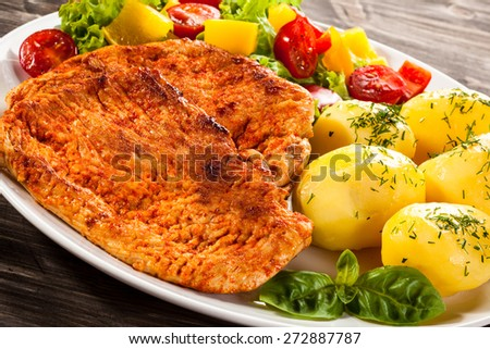 Fried pork chops, boiled potatoes and vegetable salad
