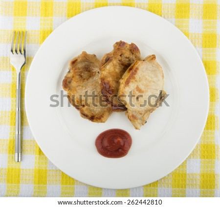 Fried pork cutlet, tomato sauce in plate on tablecloth. Top view