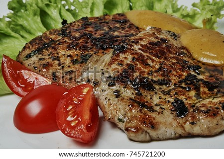 fried pork lined with slices on a plate, meat,salat,red paper,mustard