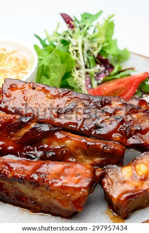 Fried pork ribs on a wooden plate decorated with salad - stock photo