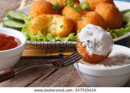 Fried potato balls with sour cream close-up. horizontal, rustic style  - stock photo