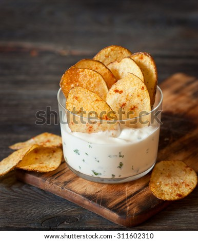 Fried potato chips with spicy sauce served in glass.