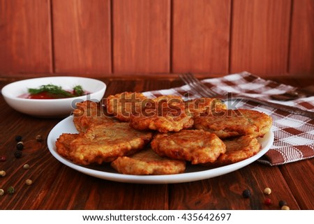 Fried potato pancakes and tomato sauce on the brown wooden background