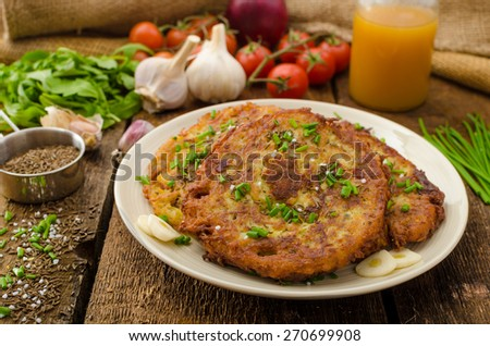 Fried potato pancakes with garlic and marjoram, sprinkled cumin, chive and coarse-grained salt - stock photo