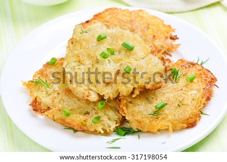 Fried potato pancakes with green onion on white plate, close up view - stock photo