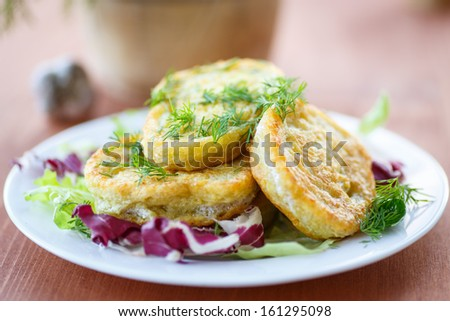 fried potato pancakes with lettuce leaves on a plate