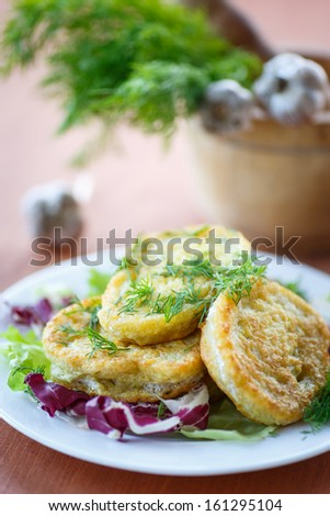 fried potato pancakes with lettuce leaves on a plate - stock photo