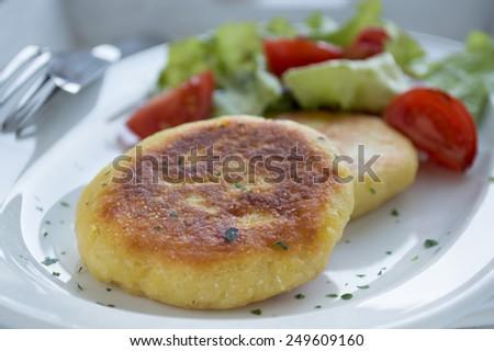 Fried potato pancakes with salad - stock photo