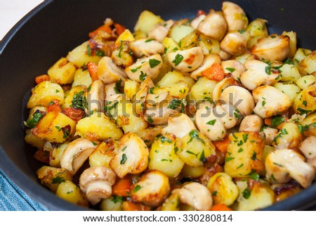 Fried potato with mushrooms in a frying pan