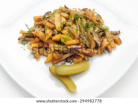 Fried potatoes and mushrooms with marinated cucumber isolated on white