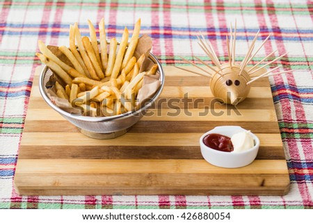 fried potatoes at home with ketchup, mayonnaise and toothpick on wooden surface - stock photo