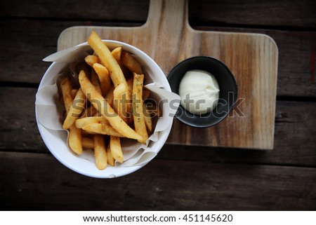 Fried potatoes french fries on wooden background - stock photo