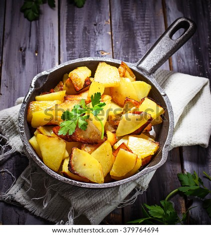 Fried potatoes in a pan. Selective focus, toned - stock photo