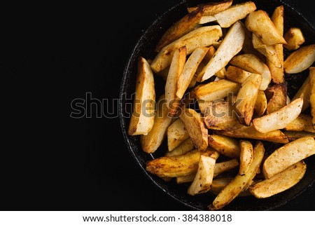 Fried potatoes on a black frying pan - stock photo
