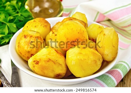 Fried potatoes on a plate on a napkin, parsley, vegetable oil, fork on a wooden boards background - stock photo