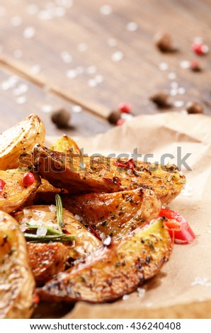 Fried potatoes on baking paper rustic serving - stock photo