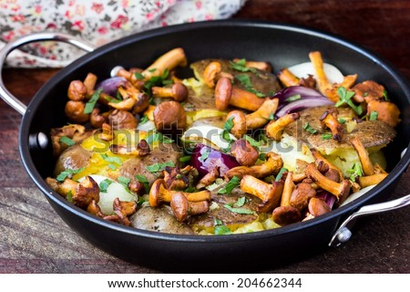 Fried potatoes with chanterelle mushrooms, onions, delicious vegetarian autumn dish, rustic style in pan